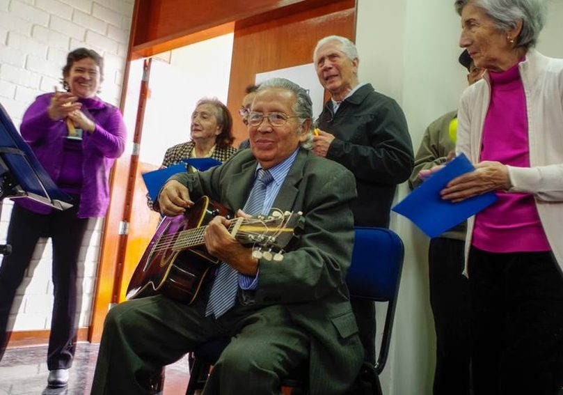 A man plays guitar, pictured here, at a memory workshop in Peru, an example of the region gearing up for a surge in dementia and establishing new standards for mental health and healthcare delivery.